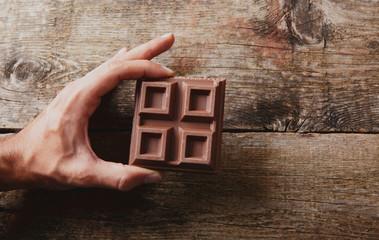Mano con cioccolata su legno