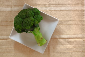 Broccoli on white dish over fabric background.