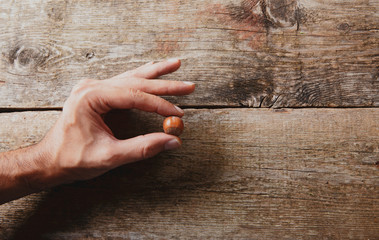 Mano con nocciola su legno