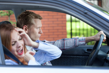 Young couple screaming in car