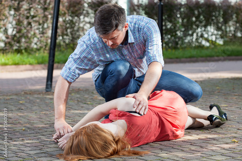 Man lying girl in recovery position - 70600839
