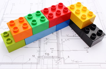Wall of colorful building blocks on housing plan