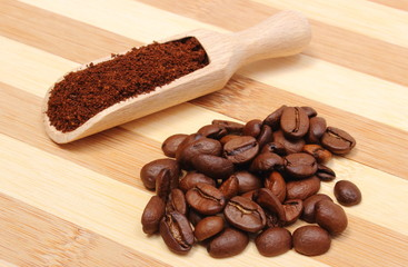 Ground and coffe grains on wooden background