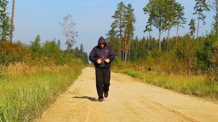 Fat man running along the forest path