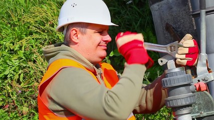 Worker with adjustable wrench fixing pipe at outdoor
