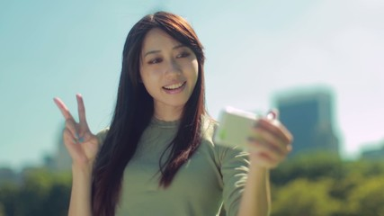 Young Asian woman in a park taking selfie photo