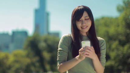 Young Asian woman in a park texting cellphone