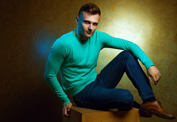 Portrait of handsome stylish man in trendy clothing sitting on c
