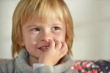 Bambino ride con mano sulla bocca