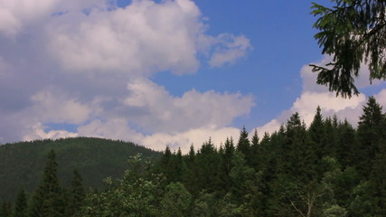 Mountain wood and beautiful blue sky with clouds.  Time lapse