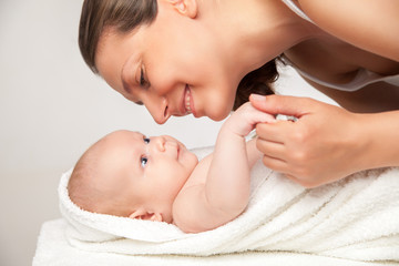 Happy mother with her baby wrapped into towel