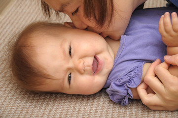Happy baby smiling playing with mother