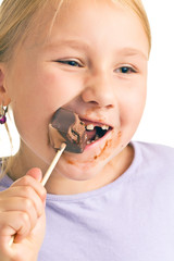 child eating chocolate lollipop