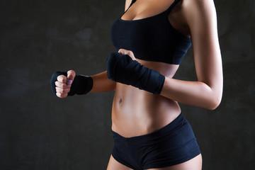Beautiful fit woman model in black hand bandage
