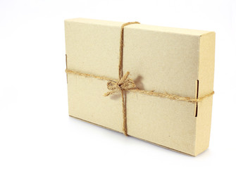 Cardboard carton wrapped with brown paper and tied with cord on