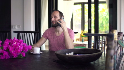 Man talking on cellphone and drinking coffee by dining table at