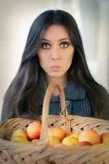 Surprised woman with a basket of ripe apples