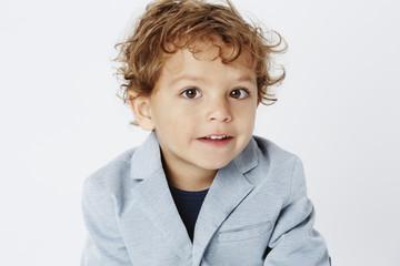 Smart young boy in suit jacket, portrait.