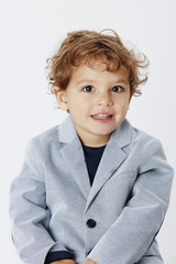 Smart and smiling young boy in suit jacket, portrait.