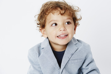 Smart two year old boy in suit looking away.