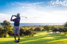 """Постер, картина, фотообои """"Man hitting golf ball down hill towards ocean and horizon"""""""