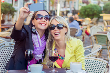 Two cheerful girls taking selfie with mobile phone