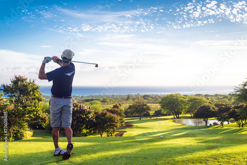 Man hitting golf ball down hill towards ocean and horizon - 70608485