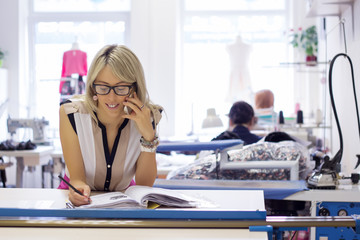 Small business owner taking customer orders by phone