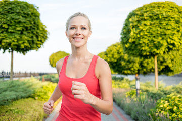 Smiling sport woman running in park