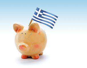 Piggy bank with cracks and national flag of Greece