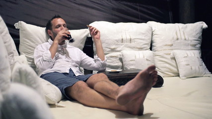 Man drinking, eating and relaxing on bed at night