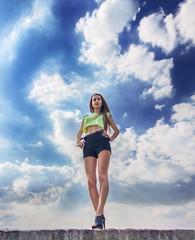 Fitness girl on the sky background