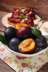 fresh plums in bowl and fruit cake on plate