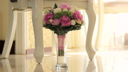 Wedding bouquet in a vase on the floor.