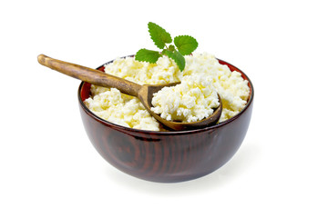 Curd in wooden bowl with spoon and mint