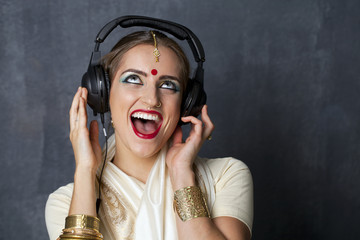 Beautiful Indian woman listening to music on headphones