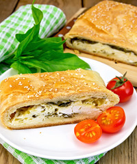 Roll filled with spinach and cheese on board with tomatoes