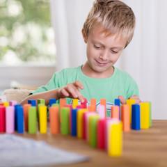junge spielt mit domino-steinen