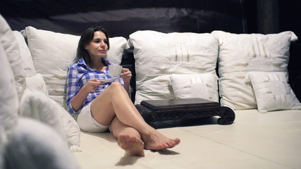 Happy woman drinking and relaxing on bed at night