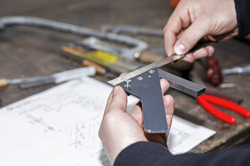 Auszubildender mit Metallwerkstück in der Gewerbeschule