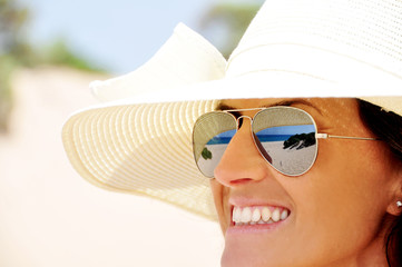 woman with hat and sunglasses with reflection of the sea