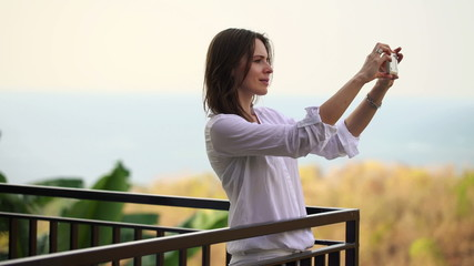 Woman taking photo of beautiful view from terrace