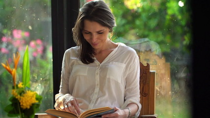 Young attractive woman reading book at home