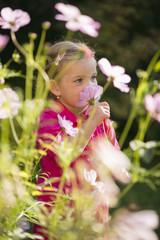 Junges Mädchen riecht Blumen im Garten