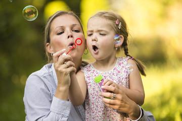 Mutter und Tochter blasen Seifenblasen im Garten