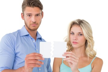 Upset couple holding torn piece of paper