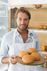 Handsome waiter holding tray of bread rolls