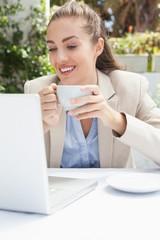 Beautiful businesswoman having a coffee using laptop