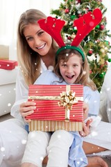 Mother and her daughter opening christmas gift