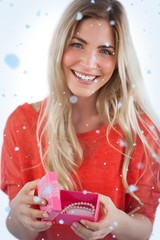 Composite image of smiling woman with gift box